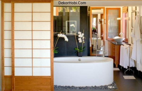 Black-granite-Japanese-bathroom-with-oval-bathtub-surrounded-by-stone-pebbles